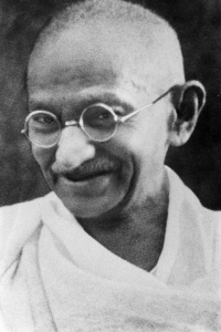 The face of Gandhi in old age—smiling, wearing glasses, and with a white sash over his right shoulder. Source: Wikipedia. Click to enlarge.